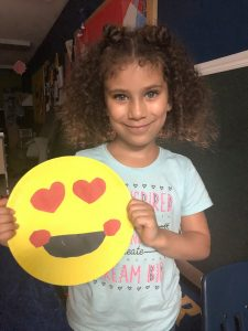 A child smiles as she shows off her artwork at our Northeast Philadelphia preschool