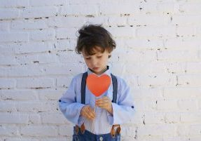 Turn Around a Bad Day With Children - A sad child holds a cutout heart.