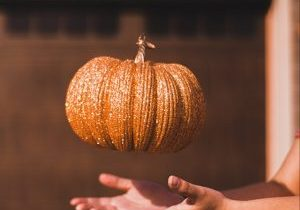 Thanksgiving Crafts for Kids - A glittery pumpkin being tossed in the air.